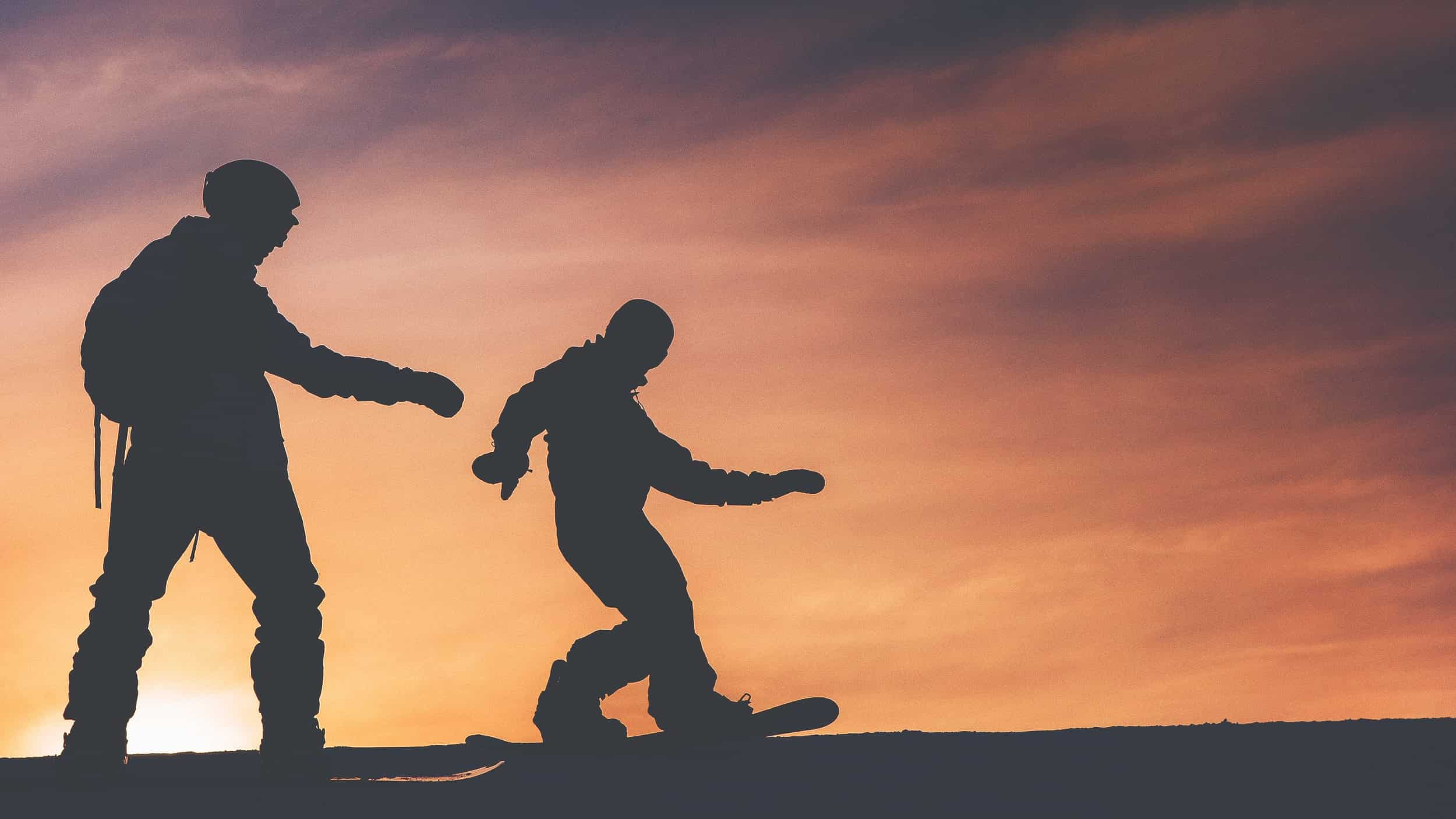 snowboarders in front of sunset